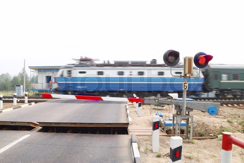 The image of railway crossing and the train. Focus is under the traffic light. Train is blurred, stock photo