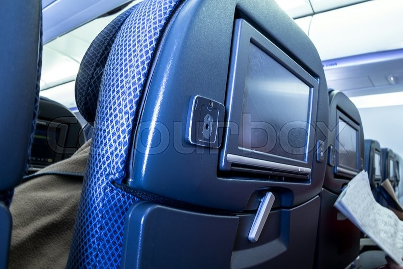 Back of modern airplane seats with small table and TV or electronic ...