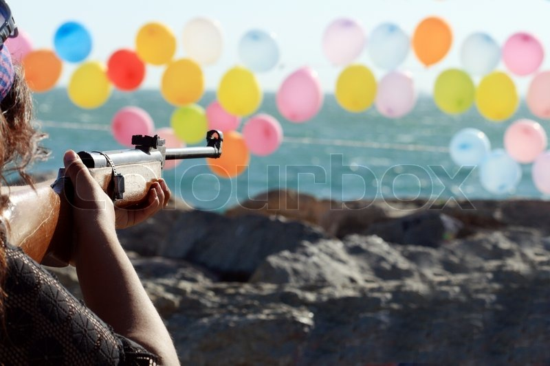 Women Shooting A Gun For Colored Balloons On Background