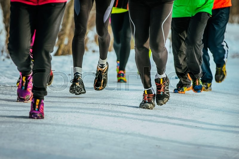 Closeup feet group athletes running snowy path in woods, stock photo