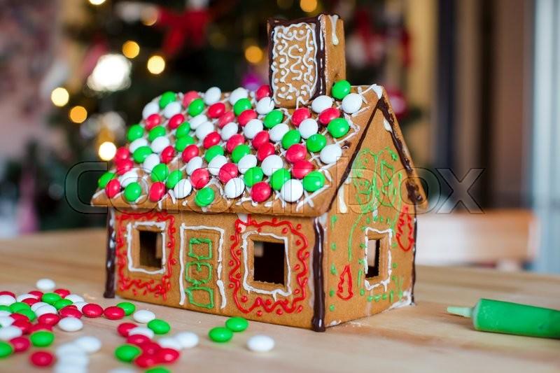 Gingerbread fairy house on a background of bright Christmas tree with light garland, stock photo