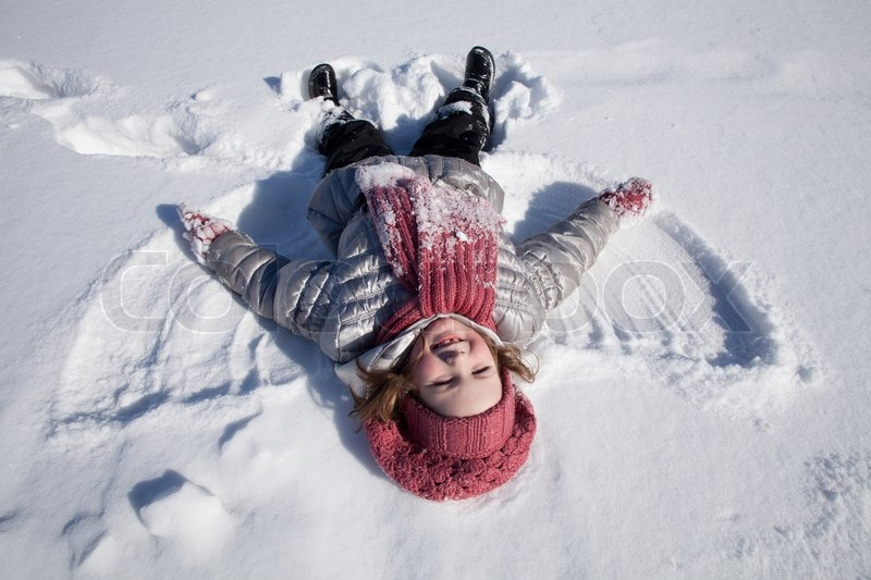 Stock image of 'The smiling girl in pink cap and scarf lays on snow'