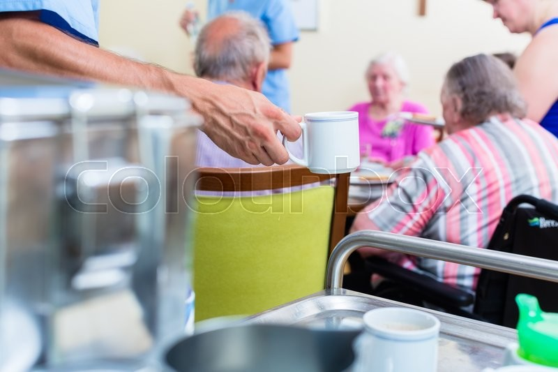 Nurse serving food in nursing home, stock photo