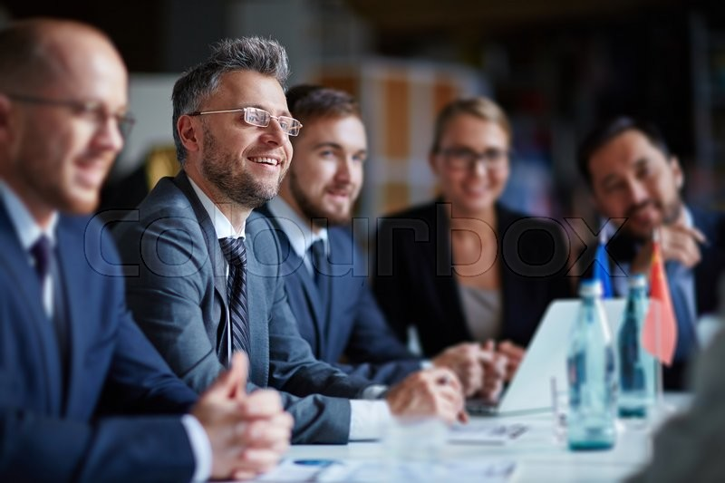 Successful businesspeople sitting at conference or seminar during lecture, stock photo