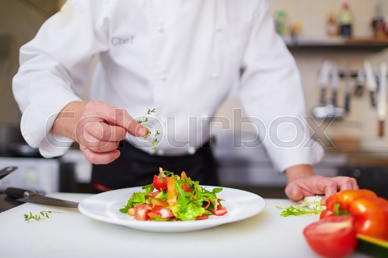 Male chef garnishing dish at the kitchen, stock photo