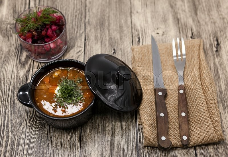 Beet salad and tomato, red pepper soup, sauce with olive oil, rosemary and smoked paprika with fork and knife on a wooden background. , stock photo