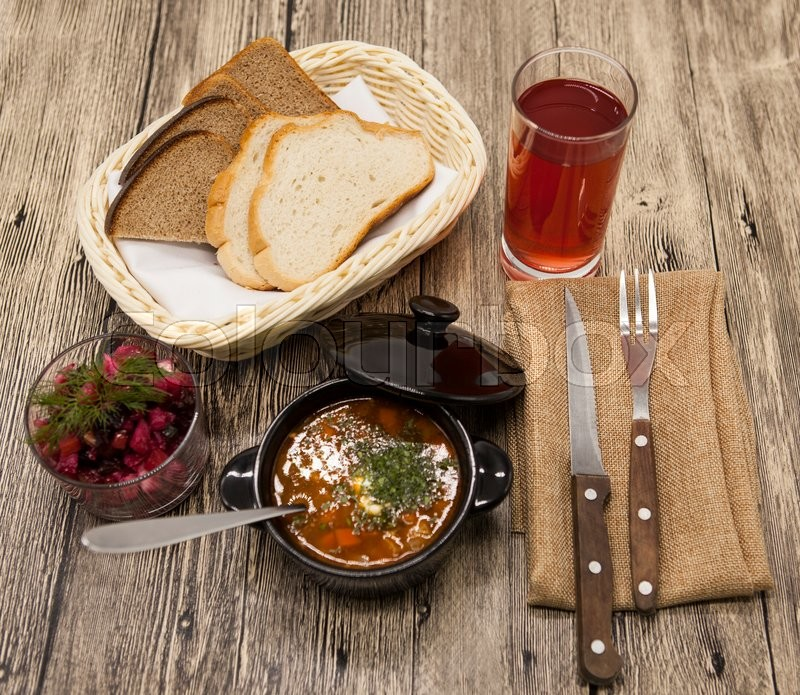 Beet salad and tomato, red pepper soup, sauce with olive oil, rosemary and smoked paprika with fork and a glass of juice and knife on a wooden background, stock photo