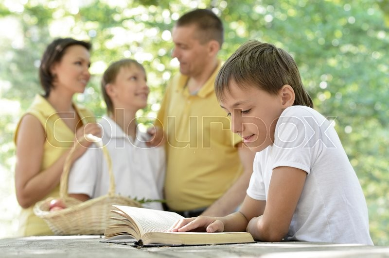 Family with kids and book outdoors in summer, stock photo