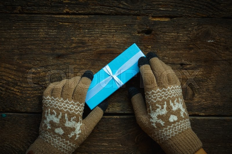 Hands in winter gloves with christmas gift box on wooden background, stock photo