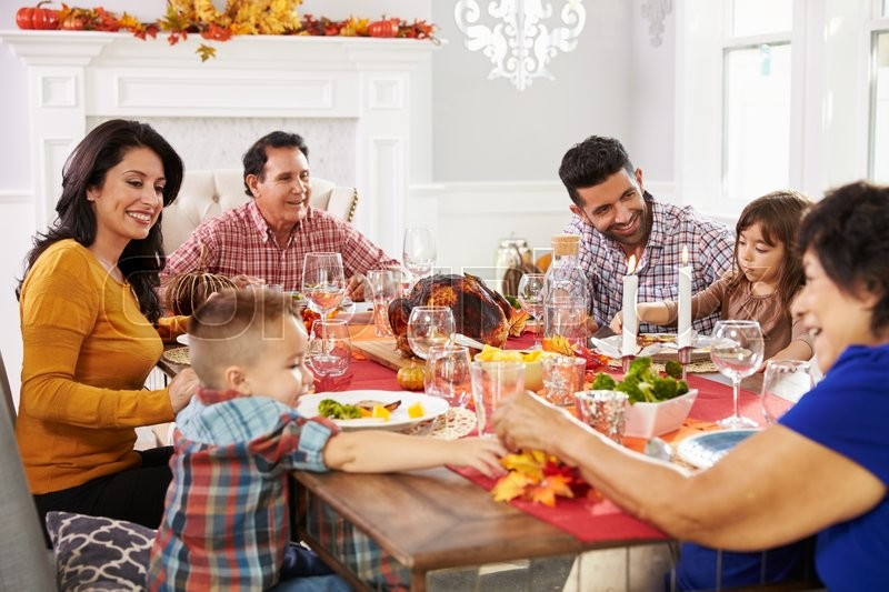 Family With Grandparents Enjoying Thanksgiving Meal At Table, stock photo