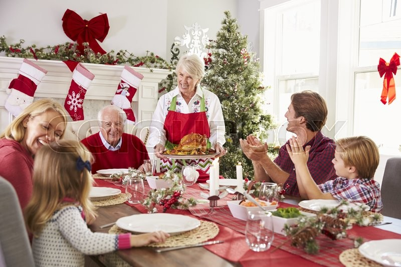 Grandmother Bringing Out Turkey At Family Christmas Meal, stock photo