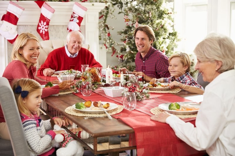 Family With Grandparents Enjoying Christmas Meal At Table, stock photo
