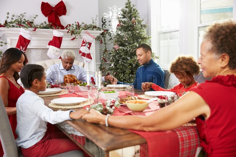 Family With Grandparents Saying Grace Before Christmas Meal, stock photo