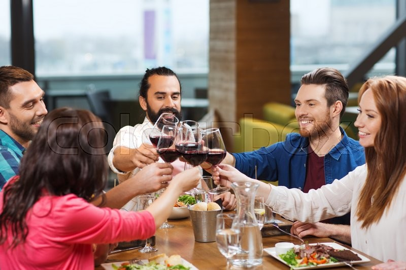 Leisure, celebration, food and drinks, people and holidays concept - smiling friends having dinner and drinking red wine at restaurant, stock photo