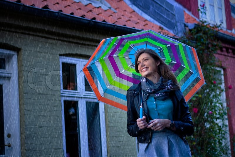 Smiling beautiful girl with her umbrella on a rainy day. Smiling beautiful girl with her umbrella on a grey day. Standing in a cute traditional scandinavian street, stock photo
