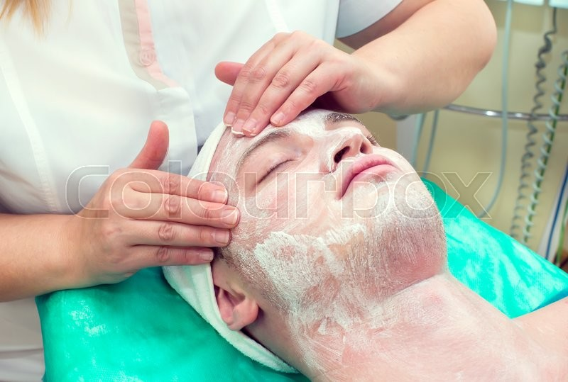 Man in the process of facials in beauty salon, stock photo