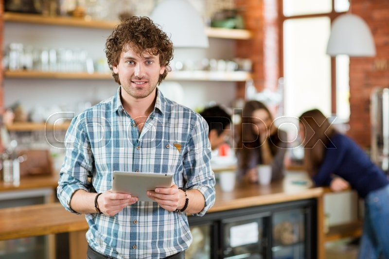 Handsome smiling young curly man in checkered shirt holding laptop stansing in hostel, stock photo