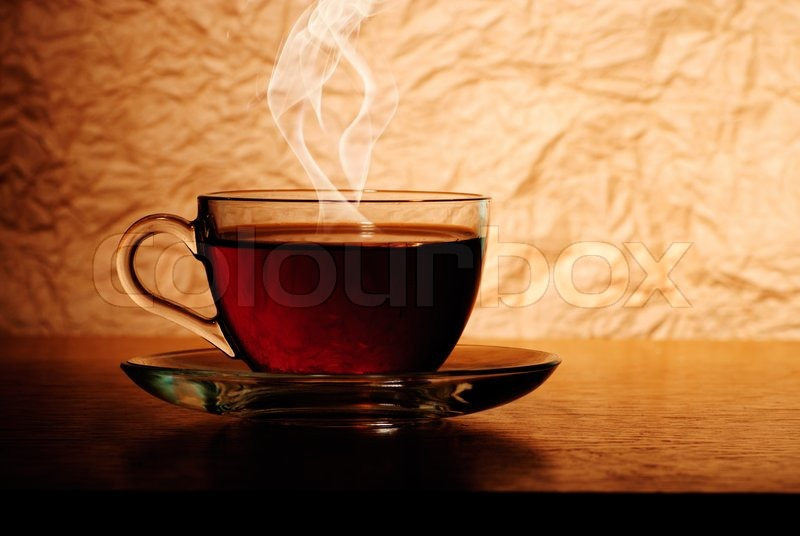 glass cup of black tea on wooden table with smoke stock photo