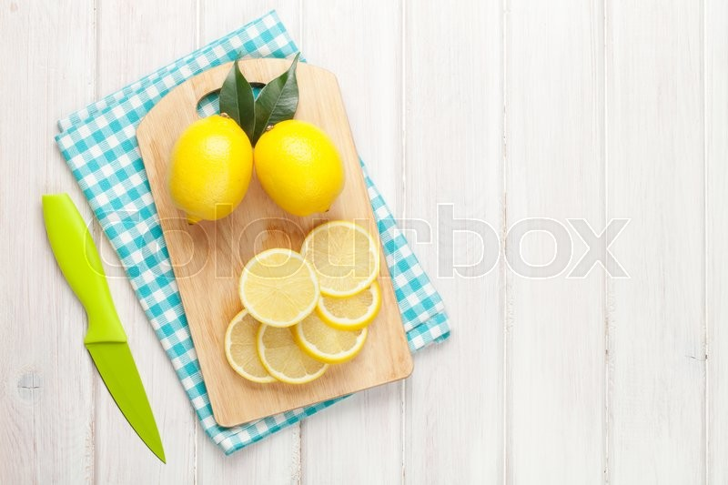 Sliced lemon on cutting board. Top view over wood table background with copy space, stock photo