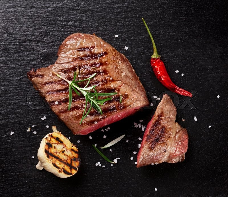 Grilled beef steak with rosemary, salt and pepper on black stone plate. Top view, stock photo