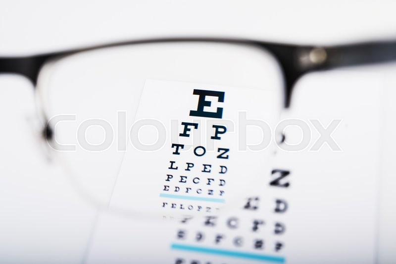 Eye glasses focus on exam chart on background, stock photo