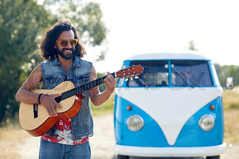 Nature, summer, youth culture and people concept - young hippie man playing guitar and singing over minivan car outdoors, stock photo