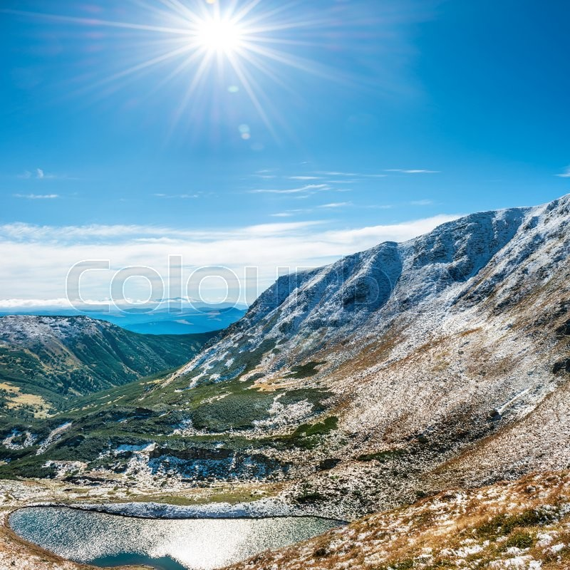 Beautiful lake in the winter mountains. Landscape with sun and snow, stock photo