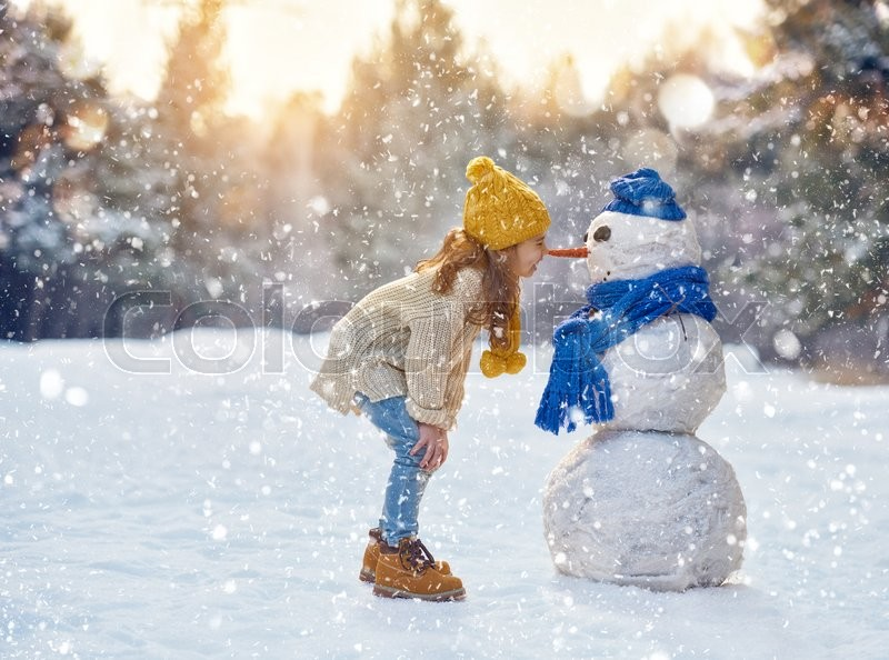Happy child girl plaing with a snowman on a snowy winter walk, stock photo