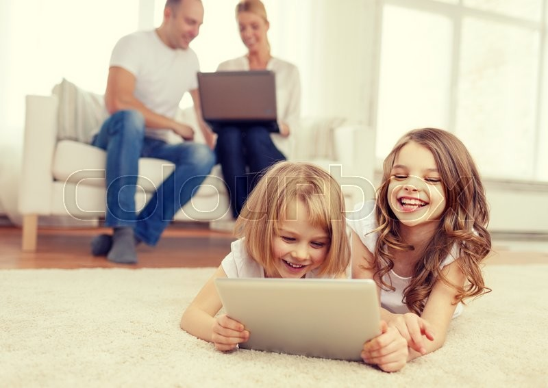 Family, children, technology and home concept - smiling sister with tablet pc computer and parents on the back with laptop, stock photo