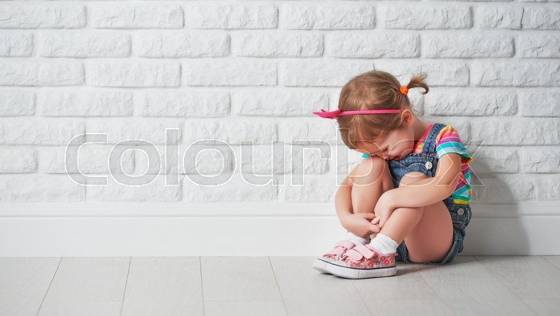Little child girl crying and sad about an empty brick wall, stock photo