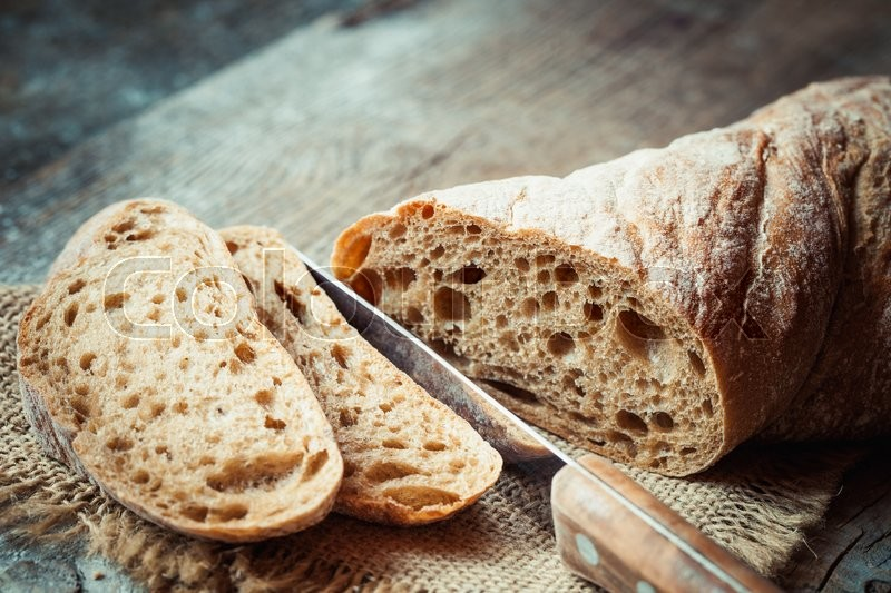 Fresh bread slice and cutting knife on rustic table, stock photo