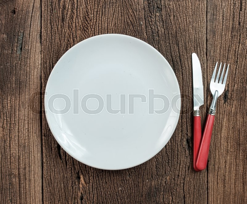 Empty white plate with silverware on wooden table. View from above, stock photo