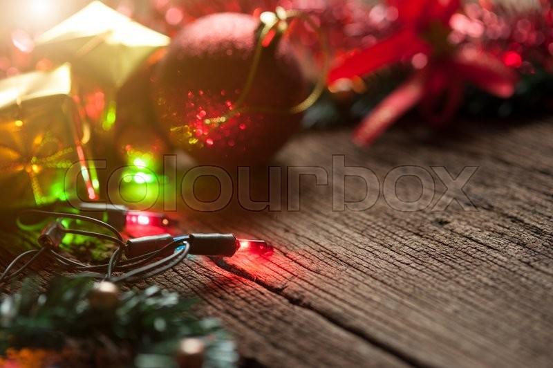 Christmas balls and colored Christmas lights on wooden table, selective focus, stock photo