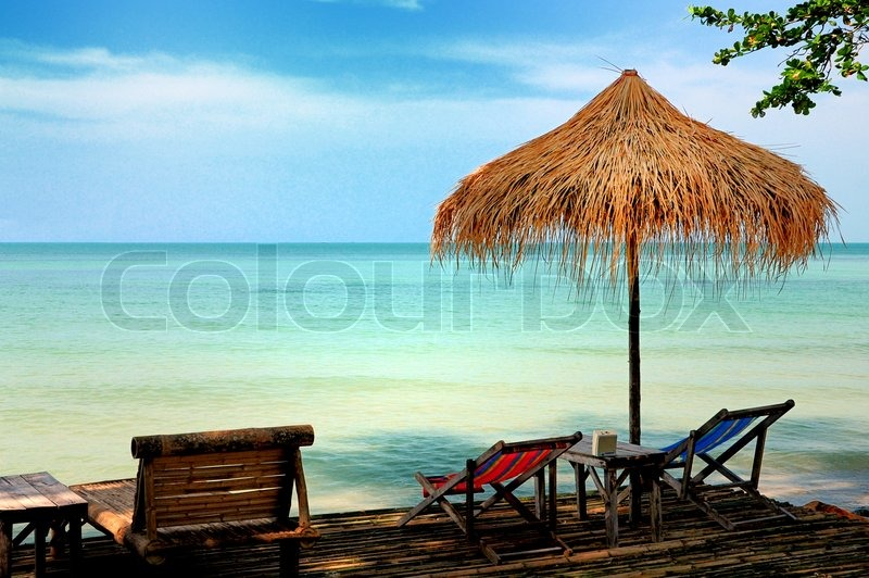 Stock image of 'Sun chair under umbrella on a tropical sandy beach'