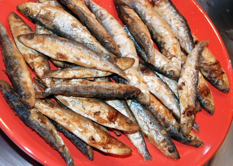 Heap of small fried fish on red plate stock photo for Fried fish nutrition