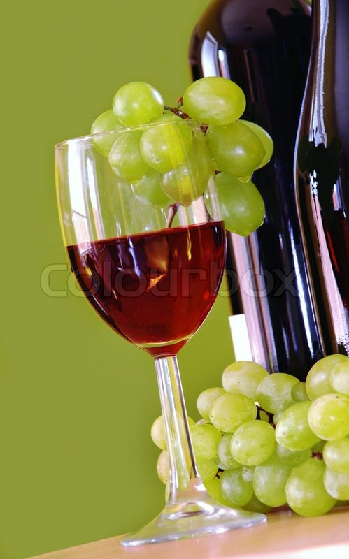 Red wine glass with grape and bottle over green stock for Red glass wine bottles suppliers