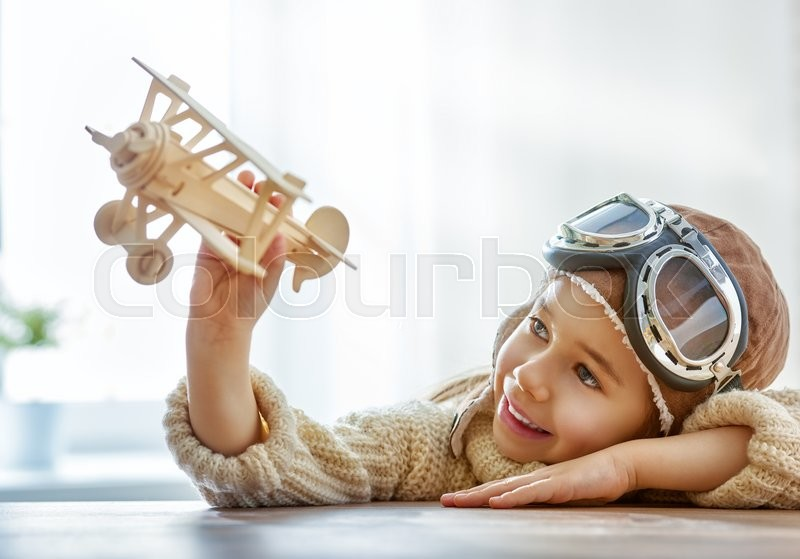 Happy child girl playing with toy airplane. the dream of becoming a pilot, stock photo