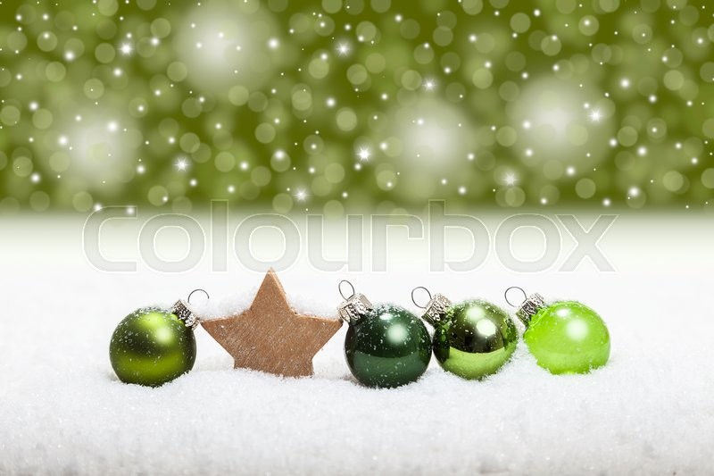 Combination of green christmas balls in the snow, stock photo