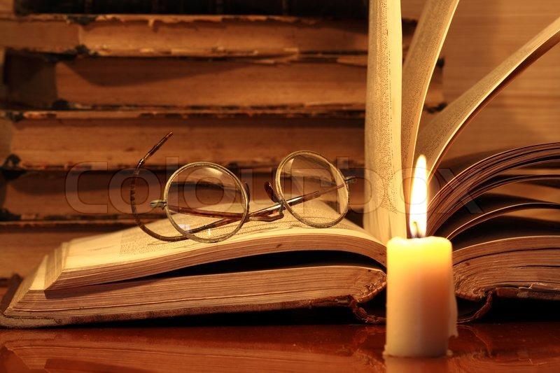 Closeup der Kerze mit brennenden Flamme auf Hintergrund  ~ Bücherregal Alt