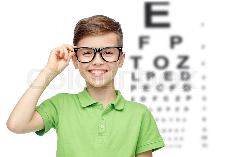 Childhood, vision, eyesight and people concept - happy smiling boy in green polo t-shirt in eyeglasses over eye chart background, stock photo