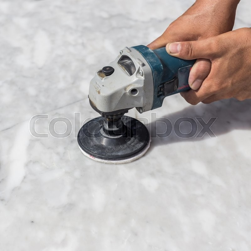 Man polishing marble stone table by small angle grinder, stock photo