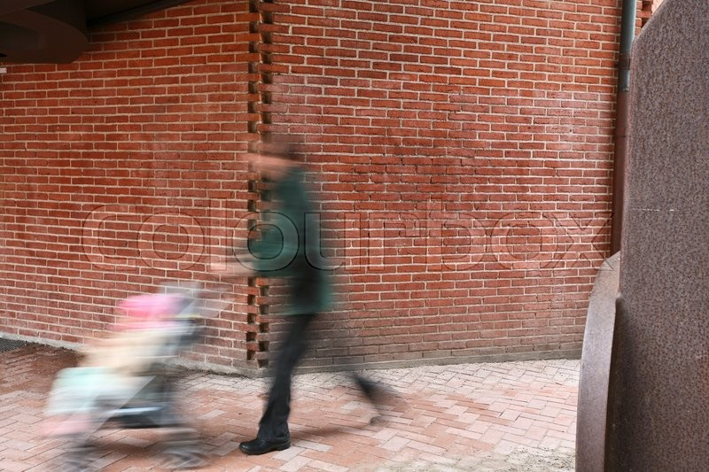 People passing by a brick wall, stock photo