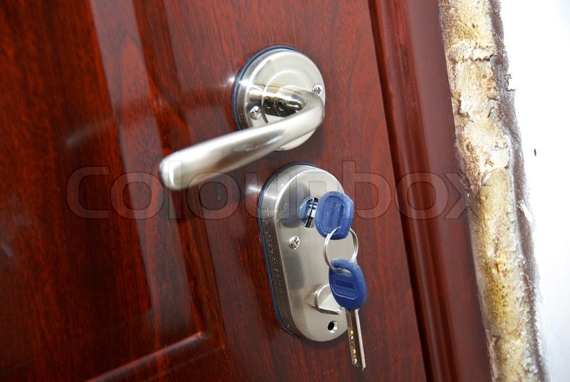 front door handle lockBrown front door with silver metallic handle and hanging keys in