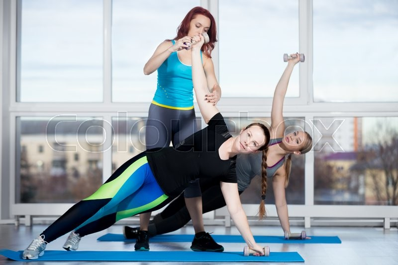 Fitness practice, group of two beautiful fit young females working out in sports club, doing side plank exercise, using dumbbells with instructor in class, full length, stock photo