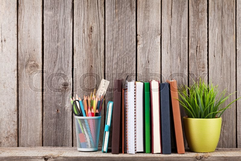 Wooden shelf with books and supplies in front of wooden wall. View with copy space, stock photo