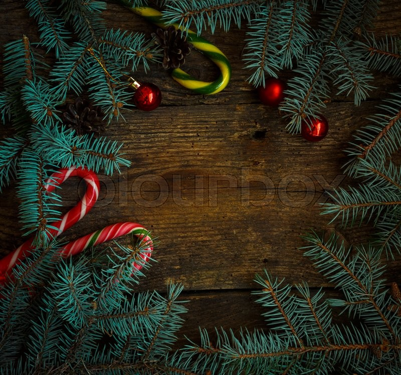 Christmas border with fir tree branches, cones, christmas decorations and candy cane on rustic wooden boards, stock photo