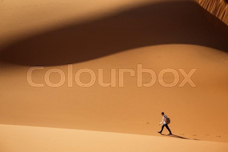 Man lost in Merzouga desert dunes, Morocco, stock photo