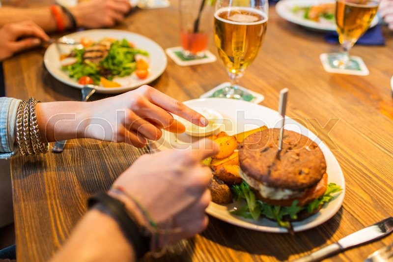 People, leisure, friendship, eating and food concept - close up of friends hands with burger at bar or pub, stock photo
