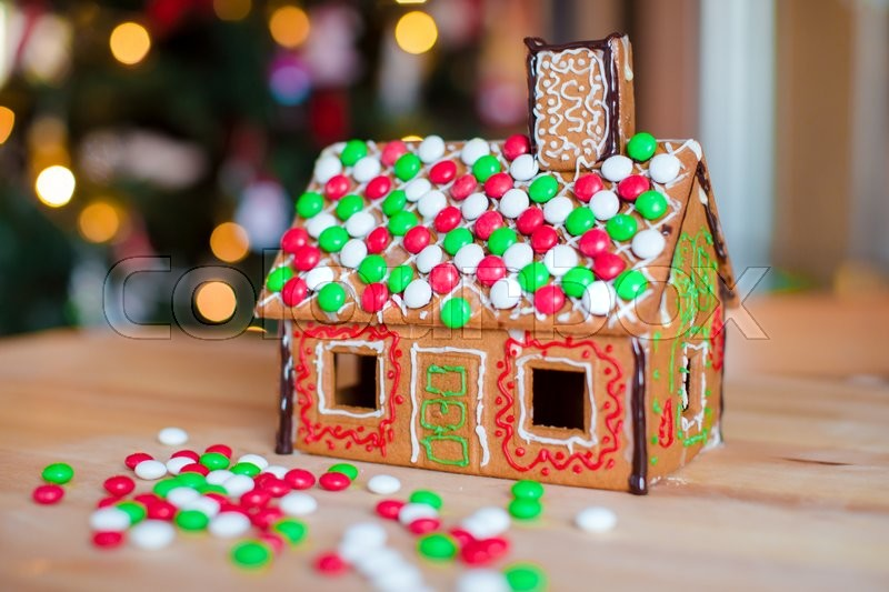 Cute gingerbread man in front of his candy ginger house background the Christmas tree lights, stock photo