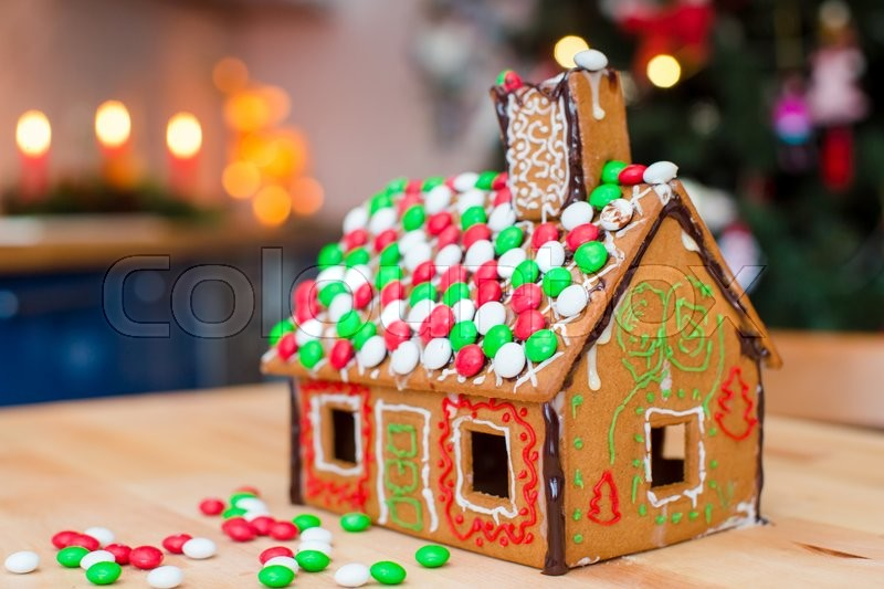 cute gingerbread man in front of his candy ginger house background the christmas tree lights stock photo colourbox